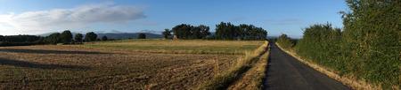 stubble field: Asphalt road and stubble field in France