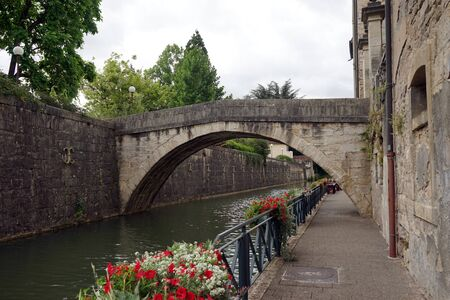 on the dole: Embankment and old arch bridge in Old town Dole, France