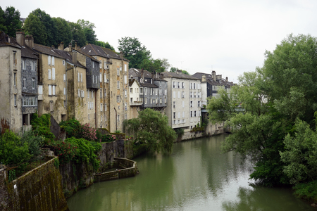 gave: OLORON-SAINTE-MARIE, FRANCE - CIRCA JULY 2015 Houses along the gave dAspe, before its junction with the gave dOssau to make the gave dOloron Stock Photo