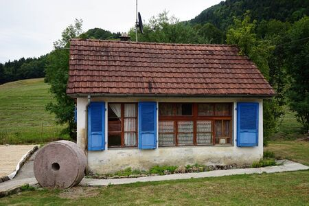 wheel house: SOUBEY, SWITZERLAND - CIRCA JULY 2015 Stone wheel near farm house Editorial