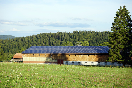 panel: Long stable with solar panel on the roof and farm field in Switzerland