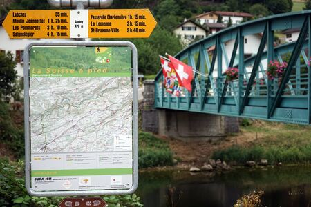 SOUBEY, SWITZERLAND - CIRCA JULY 2015 Map of hiking trails and bridge with flags on the Doubs river Editorial