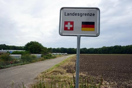 german swiss: BASEL, SWITZERLAND - CIRCA AUGUST 2015 Road sign on the Swiss - German border Stock Photo