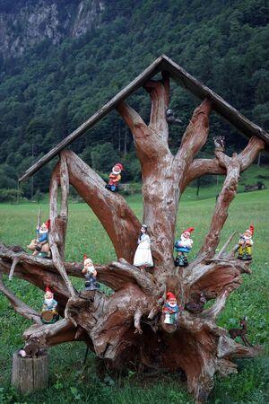 gnomos: Tronco y gnomos cerca de la carretera iin Suiza Foto de archivo