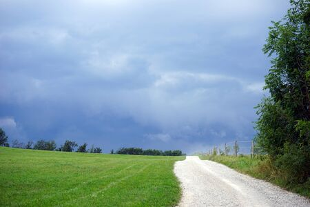 darck: Dirt road on the field and darck clouds on the sky
