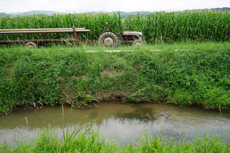 non cultivated land: Tractor and canal near green corn field, France