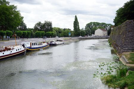DOLE, FRANCE - CIRCA JULY 2015 Wall of Old town and ships on the river Doubs Editorial