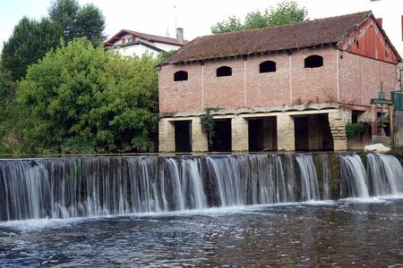 palais: SAINT-PALAIS, FRANCE - CIRCA JULY 2015 Old dam and brick house Editorial