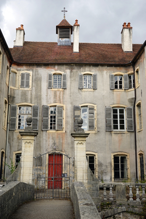 on the dole: DOLE, FRANCE - CIRCA JULY 2015 Mansion with cross in Old town