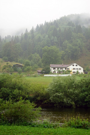 Farm house near river Doubs iand forest in Switzerland Stock Photo