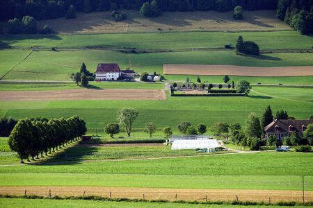 non urban: Road and farm houses in green valley in Switzerland Stock Photo