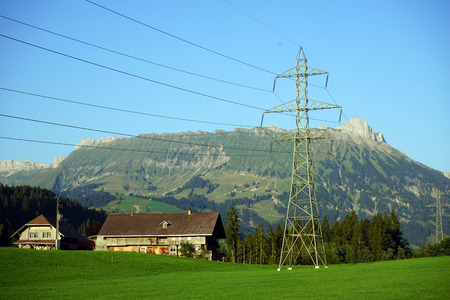 sheds: Pylon with electrical wire and sheds in farm in Switzerland