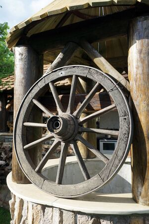wheel house: Big wheel and old well inear farm house in the village