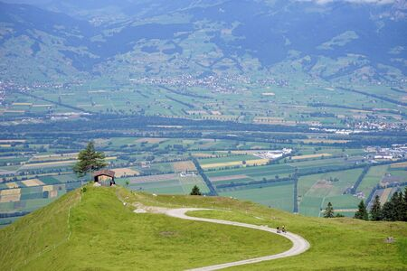 bicyclists: Road with two bicyclists and view of valley in Lichtenstein