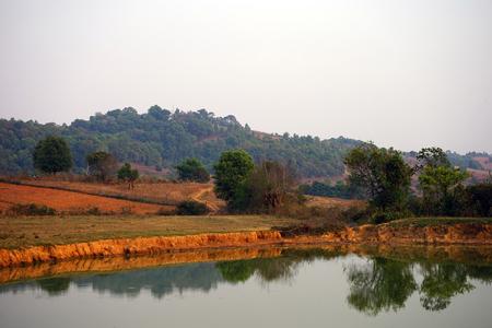 arando: Agua en estanque cerca de campos de cultivo en Myanmar