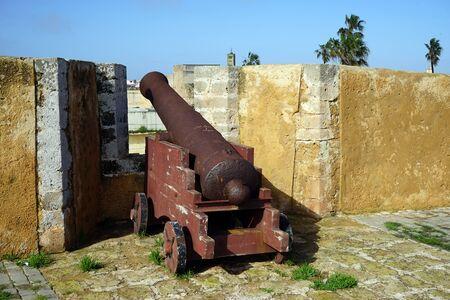 Rusty gun on he wall of fortress