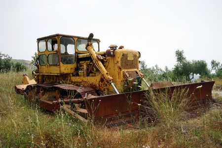 Yellow buldozer on the farmland in Crete, Greece