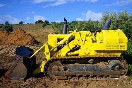 Bulldozer giallo sul campo dell'azienda agricola Archivio Fotografico