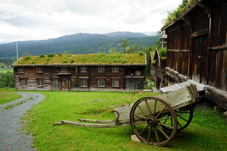 Old cart and wooden barns in farm in Norway Archivio Fotografico - 129467785