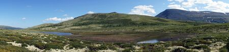 Panorama of lake and mountain in Dovre national park in Norway