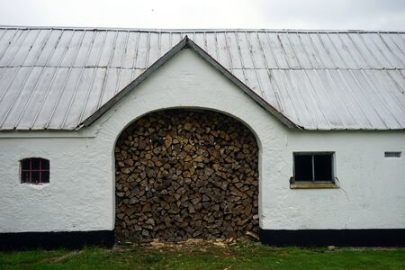 Firewood in big arch of farm house in Denmark