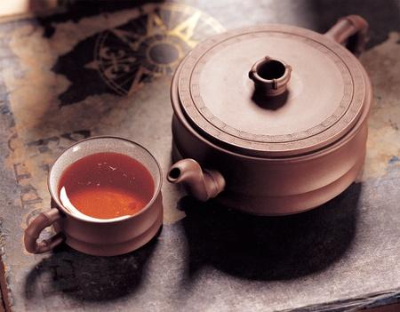 Purple pottery teapot and ceramic tea cups.