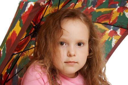 The little girl sits under an umbrella photo