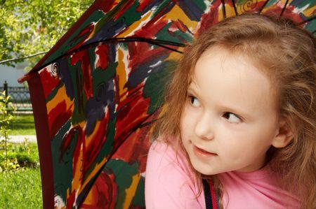 Little girl sits under an umbrella photo