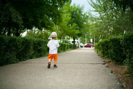 Child in loneliness goes on road from park photo