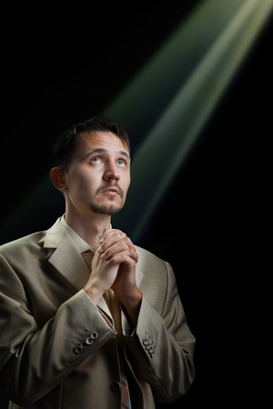 Young man in a suit, praying for something Stock Photo - 9471153