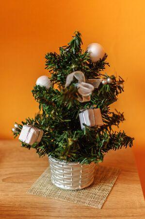 Miniature Christmas tree on the table near orange wall.