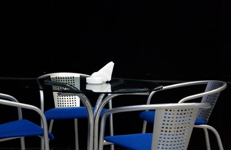 break fast: glass table and metal chairs around isolated on black