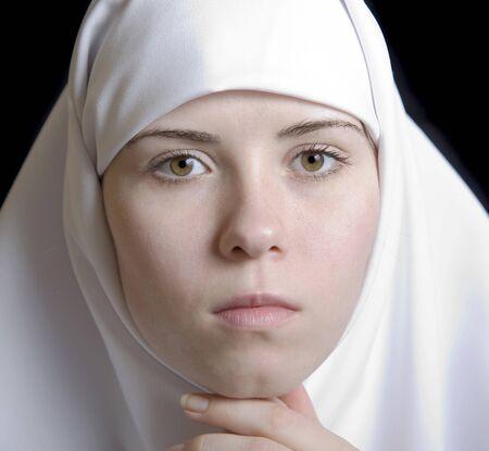 black nun: young woman nun portrait facial in white on black