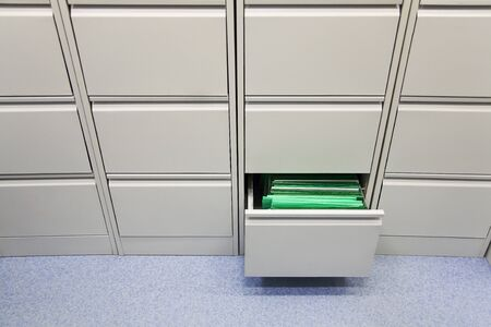 grey office file storage case with one opened box in lower row full of green files