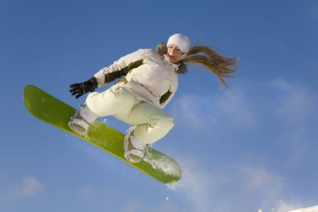 young woman on snowboard flying after jump Stock fotó