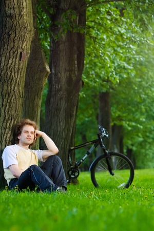 bycicle: young man siting in the park under the tree near his bycicle