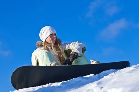 young woman with snowboard sitting on a slope Stock fotó