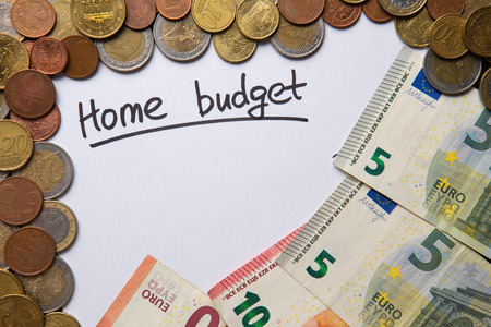 handwritten text Home Budget written and underlined on white sheet of paper, european union banknotes and coins surrounding, copyspace