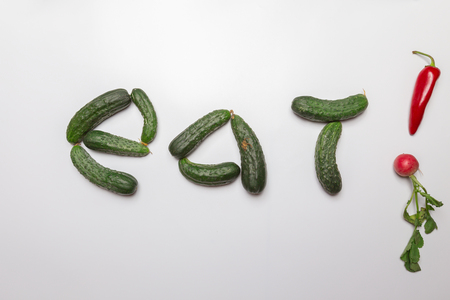 Fresh green cucumbers forming the word eat with exclamation mark formed of red pepper and radish on white background. concept of vegan, diet, healthy food