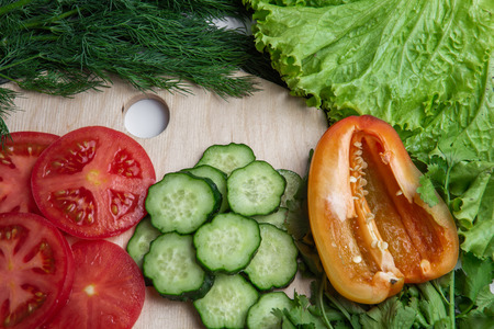 sliced cucumbers and tomatoes and pepper on a wooden board with frame formed of herbs of dill, lettuce, parsley, closeup, top view