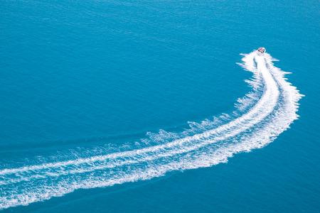 Motoscafo in mare con schiuma di scia sull'acqua blu
