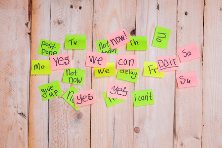 motivating phrases like Now, can do it, Yes, on colour sticky notes above demotivating text like I Can not, not Today,delay, give up posted to wooden board Stock Photo