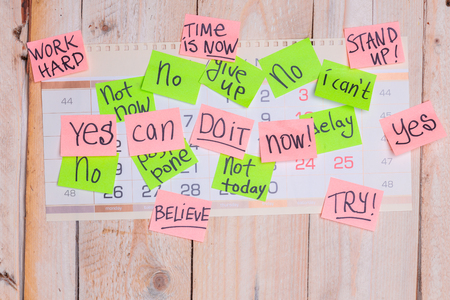 motivating phrases like Now, can do it, Yes, on colour sticky notes above demotivating text like I Can not, not Today,delay, give up posted to wall calendar on wooden board