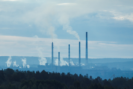 refinery with smoke stacks in a distance and forest in foreground, ecology problem, polution.