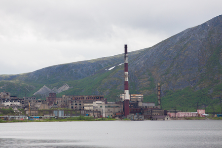 old abandoned refinery with high stacks in a distance surrounded by mountains, ecology problem, polution. Stock Photo