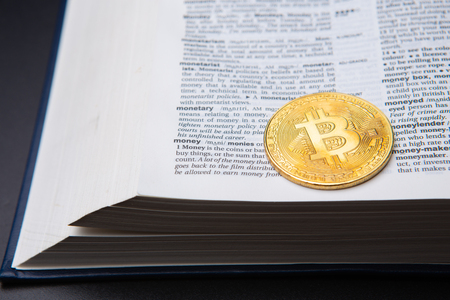 A table with book and bitcoin on a page with Money definition. Learning crypto currency. Concept, a new educational subject