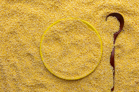 Yellow dry uncooked millet background, top view, vertical Reklamní fotografie