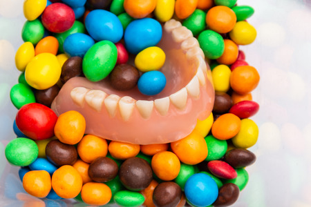 Pile of candy and dental prothesis in color sweets bonbons, concept, oral teeth care, harmful food, top view, closeup