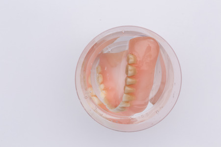 Close up of dental prothesis in glass of water on white background, above view closeup