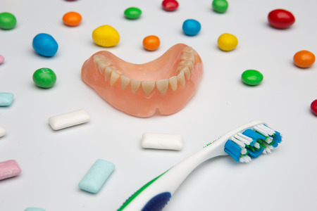 different colors sweets bonbons and chewing gum, dental prothesis, tooth brush and toothpaste, concept, oral teeth care and prevent, harmful food, top view, closeup. on white background